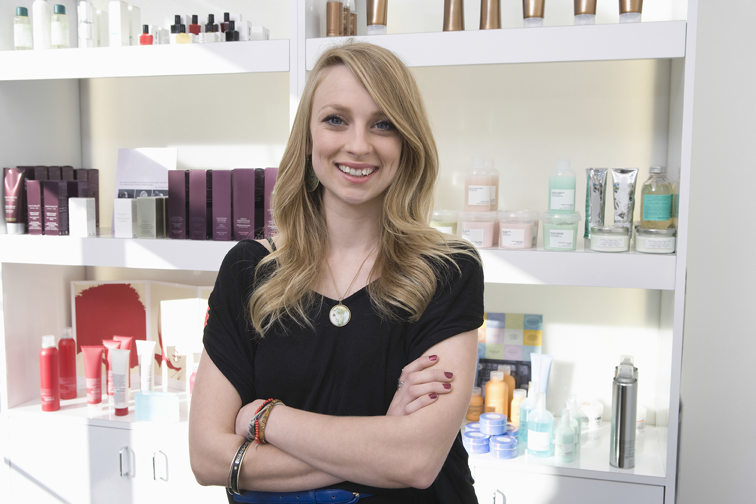 Hair salon business owner standing in front of hair product shelves