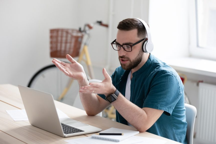 Man sitting at table at home with laptop studying for online classes