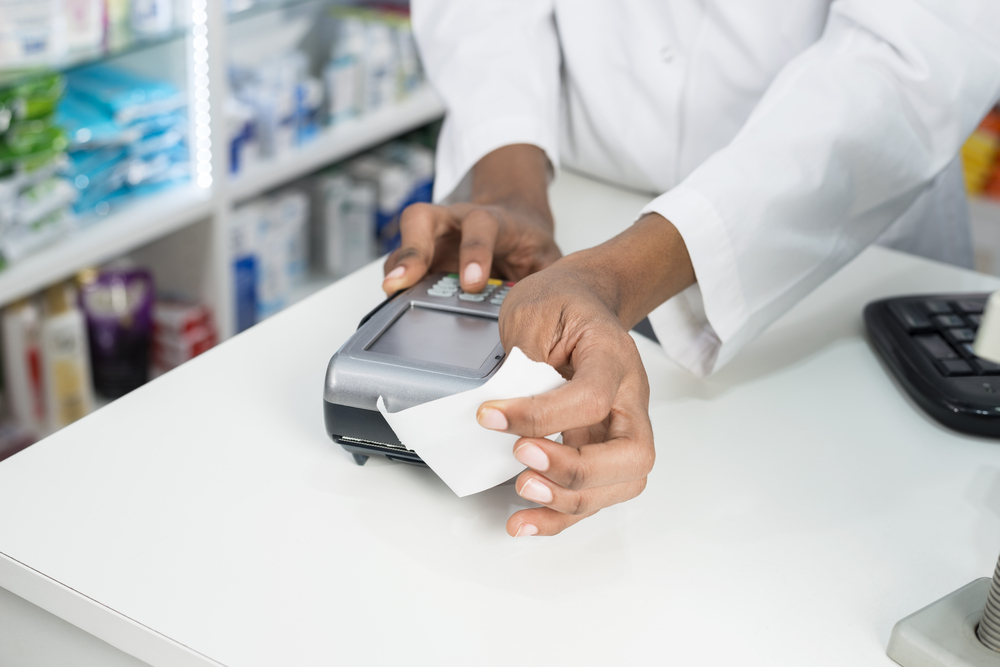 Pharmacist holding a receipt coming out of a portable printer