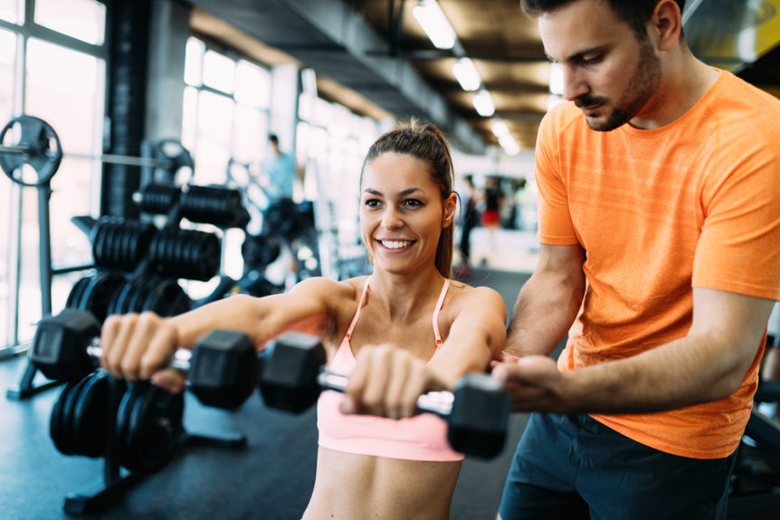 Male personal trainer helping woman lift two weights