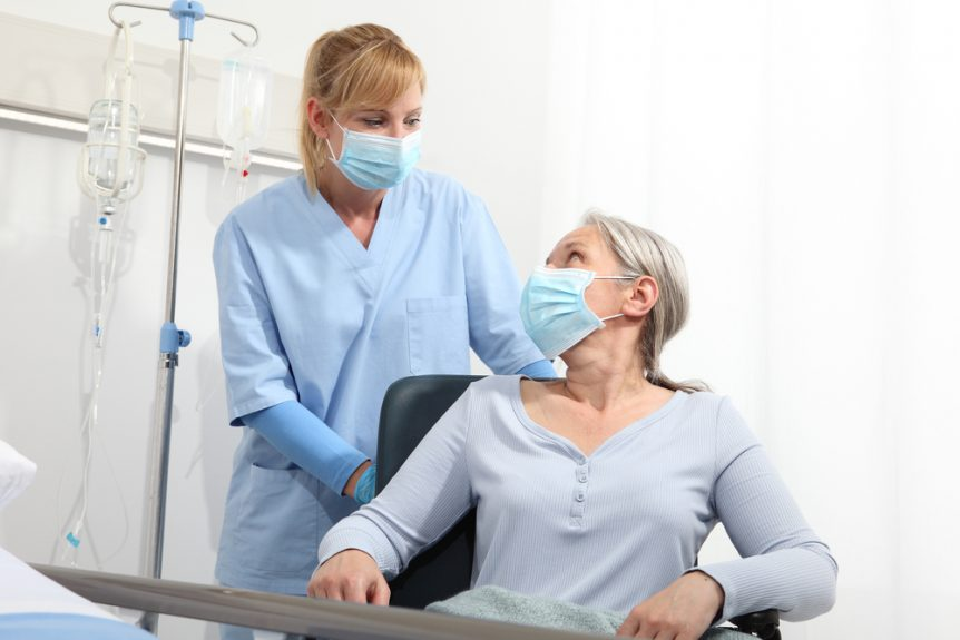 Medical assistant wearing mask helping a patient