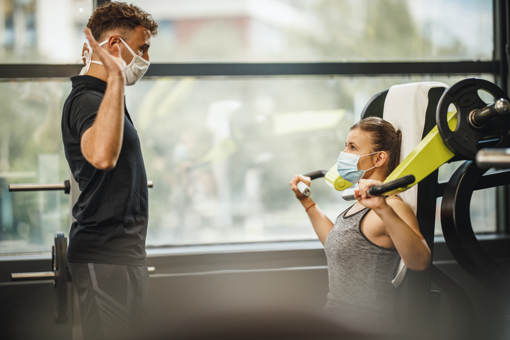 Young woman using weight machine with personal trainer watching wearing masks