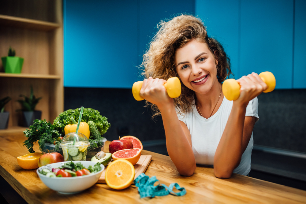 Personal trainer holding small weights surrounded by nutritious foods
