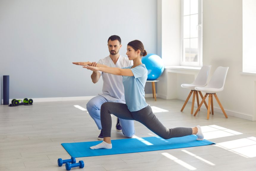 Fitness Trainer Helping a Young Woman