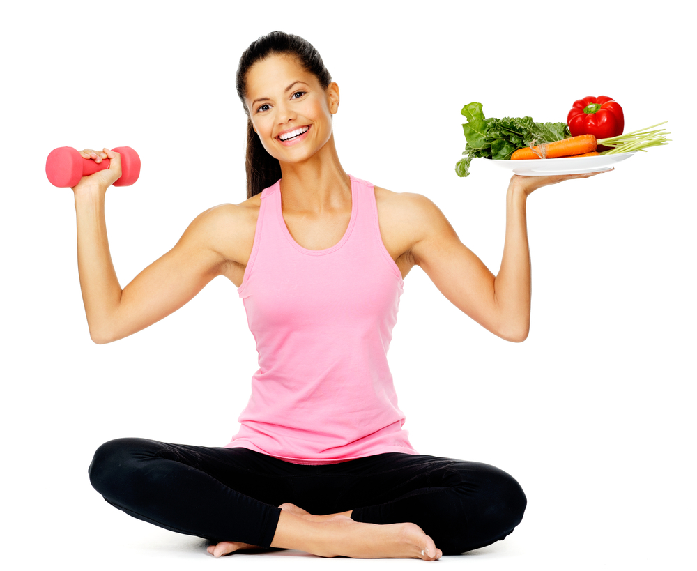Healthy woman holding a hand weight and plate of vegetables