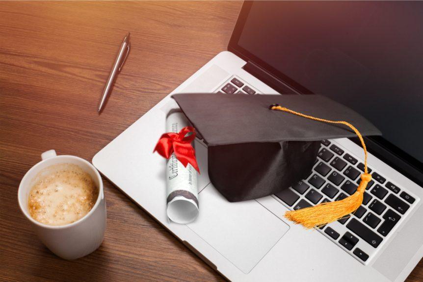 Graduation cap and diploma sitting on laptop