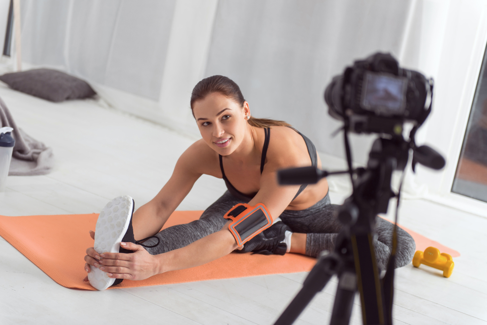 Sporty Woman Stretching on a Mat and Making a Workout Video