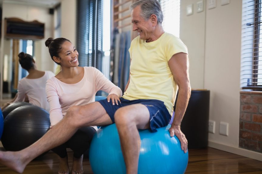 Young Woman Helping a Senior Man Exercise