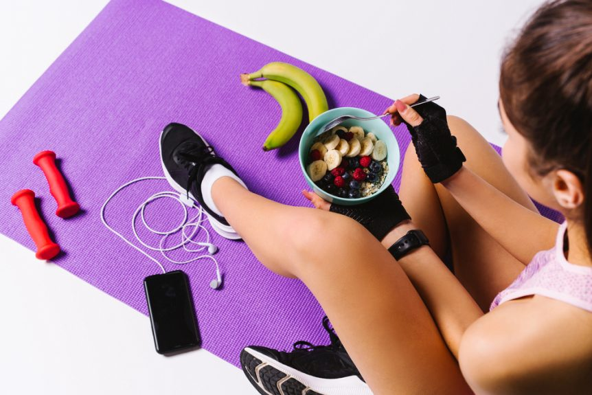 Young girl eating nutritious food sitting on an exercise mat